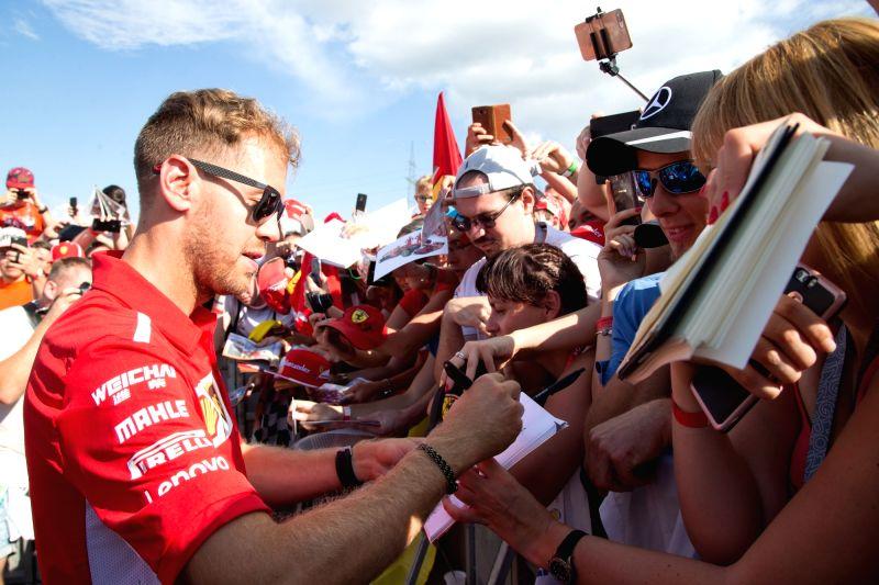 MOGYOROD, July 27, 2018 - Ferrari's driver Sebastian Vettel (L) of Germany signs autographs ahead of the Hungarian F1 Grand Prix on the Hungaroring circuit in Mogyorod, Hungary on July 26, 2018.