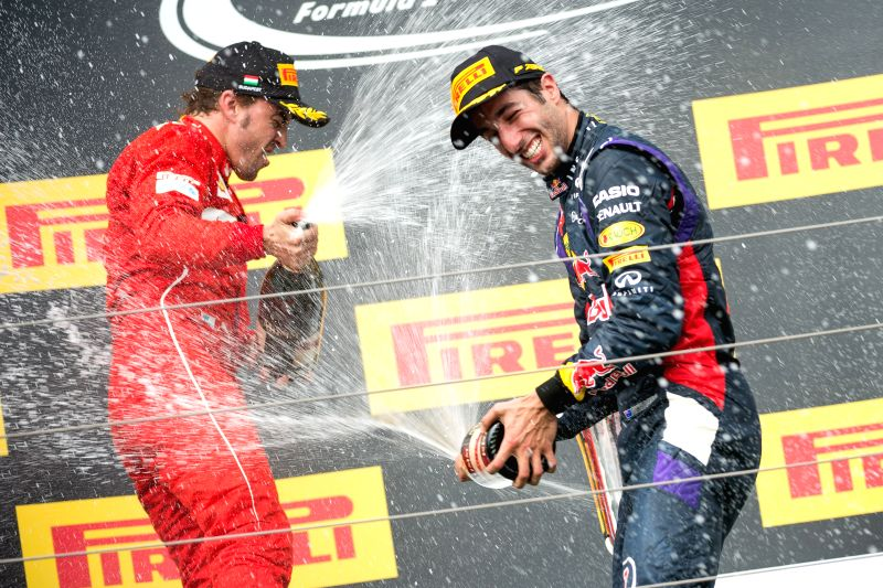 Red Bull Formula One driver Daniel Ricciardo (R) of Australia sprays the champagne with Ferrari Formula One driver Fernando Alonso of Spain during the awarding ...