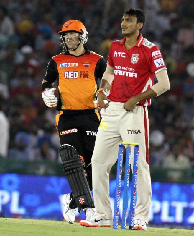 Sunrisers Hyderabad batsman David Warner and Axar Patel of Kings XI Punjab during an IPL-2015 match between Sunrisers Hyderabad  and Kings XI Punjab at  Punjab Cricket Association Stadium in ... - David Warner and Axar Patel