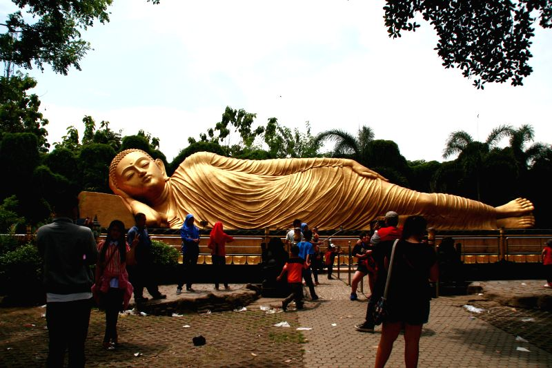 People take photos of the world's third largest Sleeping Buddha statue at Mojokerto in East Java, Indonesia