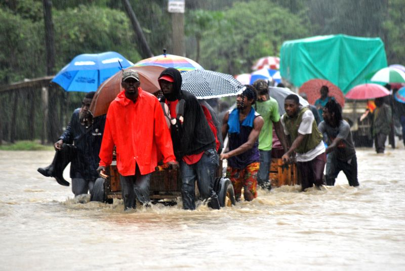 MOMBASA, May 8, 2017 - Local residents walk through water in a flooded area in Mombasa, Kenya, May 8, 2017. At least six people were killed on Monday after a perimeter wall collapsed on their ...