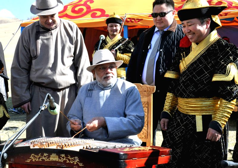 Prime Minister Narendra Modi playing a traditional Mongolian music instrument ``Yochin`` at Mini Naadam Festival, in Ulaanbaatar, Mongolia on May 17, 2015. - Narendra Modi