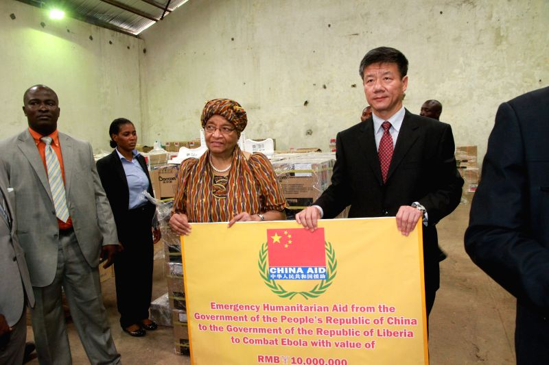 Chinese Ambassador to Liberia Zhang Yue (1st R) and Liberia's President Ellen Johnson-Sirleaf (2nd R) pose for photos during a handover ceremony in Monrovia, ...