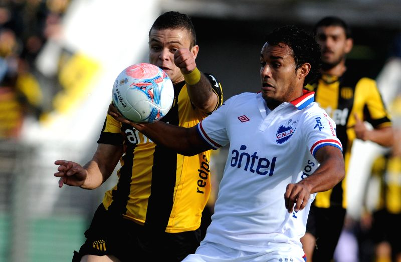 The player Jonathan Rodraguez (L) of Penarol, vies the ball with Ismael Benegas (R) of Nacional, during the soccer game of the Uruguayan Closing Tournament in ..