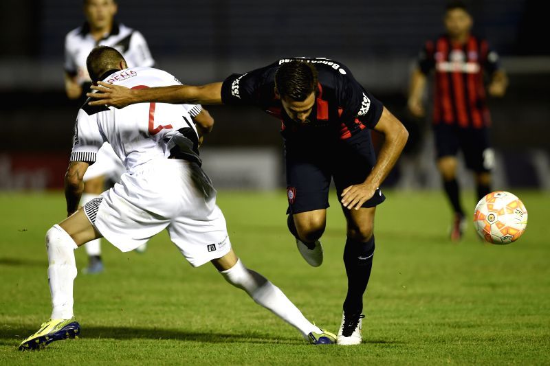 Danubio's Agustin Pena (L) of Uruguay vies for the ball with San Lorenzo's Emanuel Mas of Argentina during the match of Libertadores Cup, at Centenario Stadium, ...