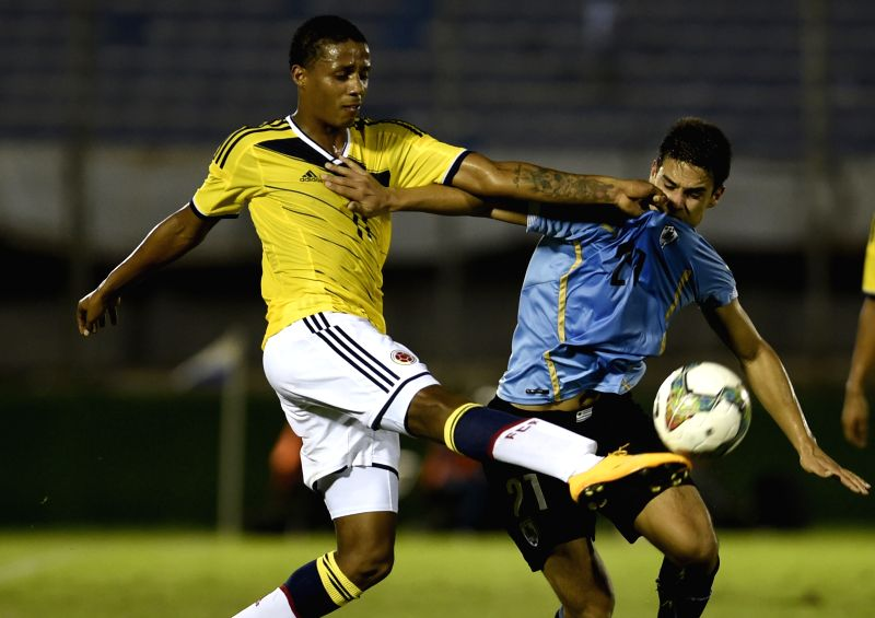 Uruguay's Guillermo Cotugno (R) vies for the ball with Colombia's Jeison Lucumi during their final phase match of the South American U-20 tournament at the ...