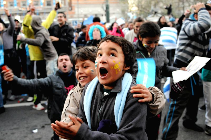Uruguay's fans cheer while watching a Group D match between Uruguay and England of 2014 FIFA World Cup on a screen in downtown Montevideo, capital of Uruguay, on