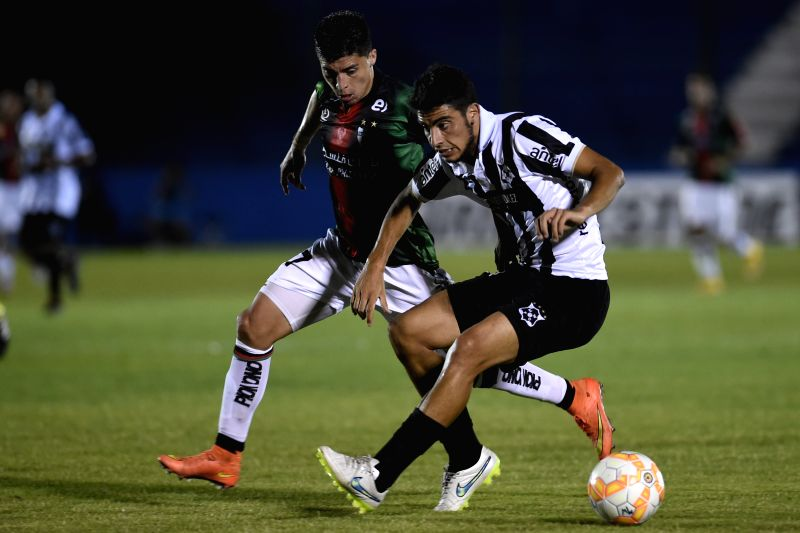 Wanderers's Gaston Rodriguez (R) of Uruguay vies for the ball with Palestino's Esteban Carvajal of Chile during the match of Copa Libertadores in the Gran ...