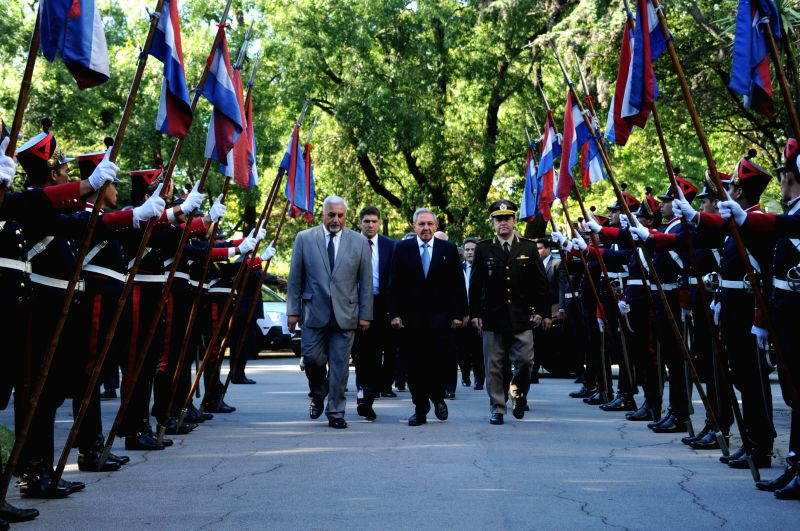 Image provided by Uruguay's Presidency shows Cuban President Raul Castro (C) reviewing the guard of honor ahead of his talks with Uruguay's President Tabare ...