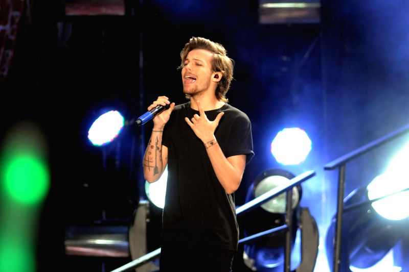 "Louis Tomlimson, member of British band One Direction, performs during a concert of their ""Where we are"" tour, in the Centenario Stadium, in Montevideo, ."