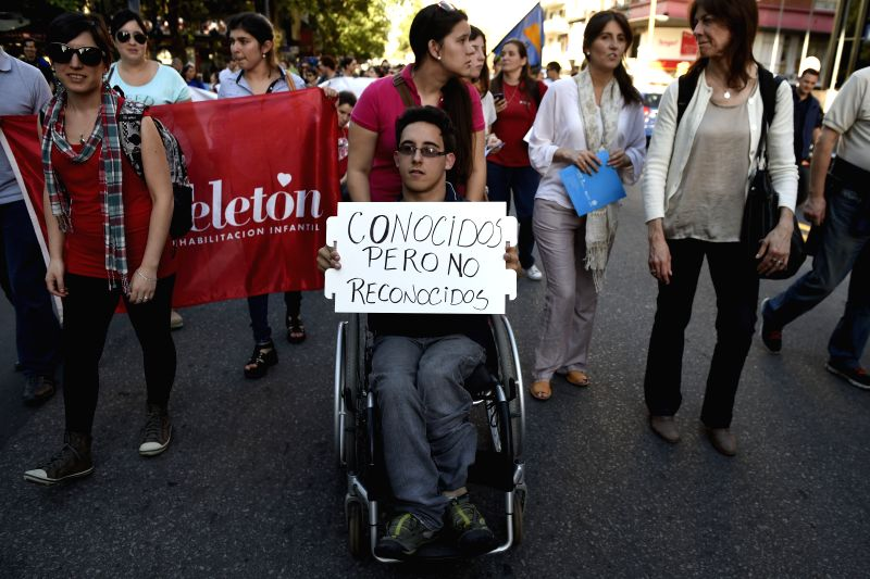 Montevideo (Uruguay): A person with a disability holds a banner during the March for Accessibility and Inclusion marking the International Day of People with Disabilities in Montevideo, capital of ...