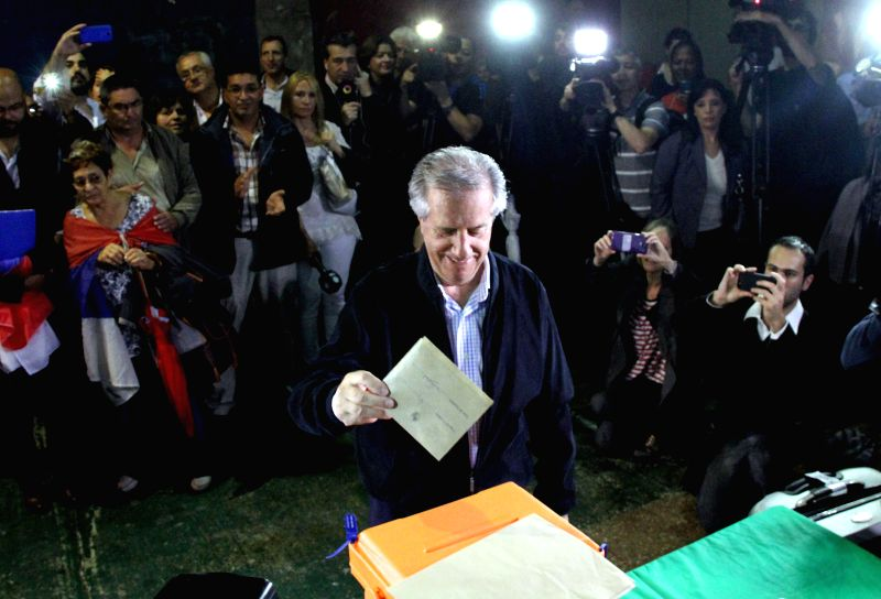 Montevideo (Uruguay): Presidential candidate of Broad Front party, Tabare Vazquez (front), casts his ballot at a polling station, in Montevideo, capital of Uruguay, on Nov. 30, 2014. Voters in ...