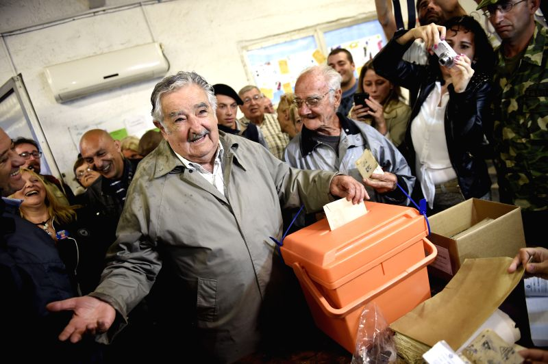 Montevideo (Uruguay): Uruguay's President Jose Mujica (C), casts his vote in a polling station, in Montevideo, capital of Uruguay, on Nov. 30, 2014. Voters in Uruguay are heading to the polls on ...