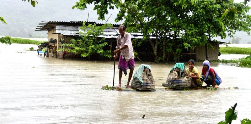 Morigaon: People move to higher places in flood hit Morigaon, Assam. (Photo: IANS)