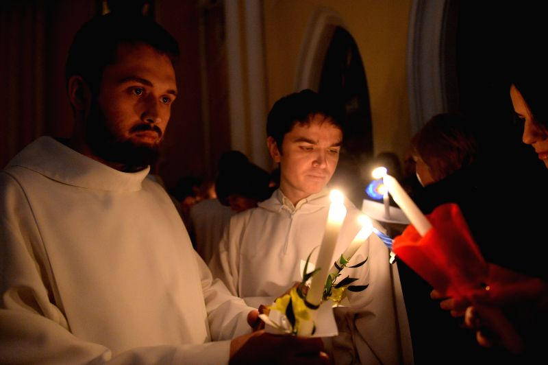Priests share Easter fire with worshippers during the Easter service at the Cathedral of the Immaculate Conception in Moscow, Russia, April 4, 2015. (Xinhua/Pavel ...