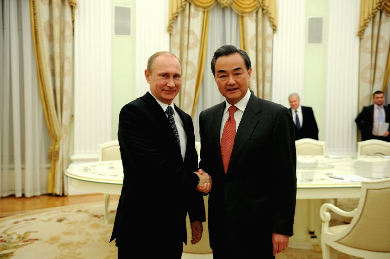 Russian President Vladimir Putin (L) meets with Chinese Foreign Minister Wang Yi (R) in Moscow April 7, 2015. - Wang Y
