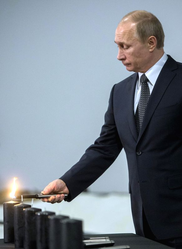Russian President Vladimir Putin lights a candle during a ceremony marking the 70th anniversary of the liberation of the Auschwitz concentration camp at the Jewish ..