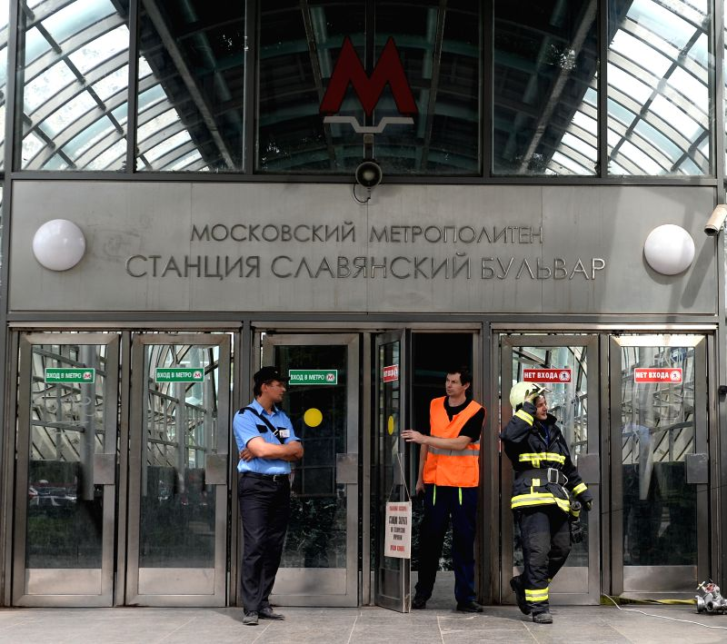 Rescuers and repair personnel stand outside the Slavyanski Bulvar subway station in Moscow, capital of Russia, on July 15, 2014. At least 16 people have been ... - Vladimir Puchkov