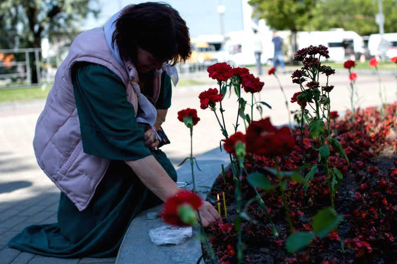 A woman lights a candle near Park Pobedy station on July 16, 2014, in Moscow, Russia. Residents in Moscow laid flowers and lighted candles at the metro station to ...