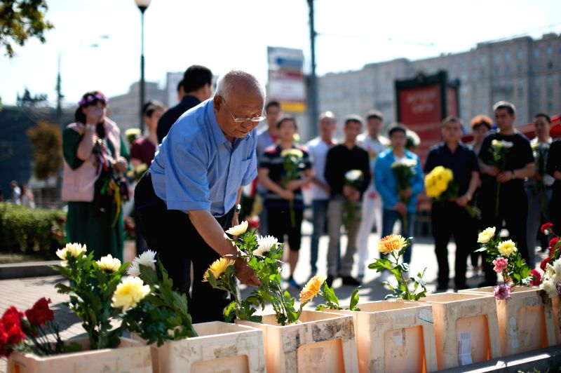 An old man lays flowers for the victims of Moscow's subway derailment to convey his condolences in Moscow, Russia, July 17, 2014. At least 22 people died and ...