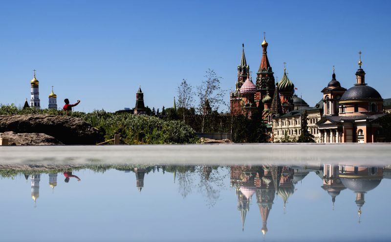 A visitor takes photos in a park near the Red Square in Moscow, Russia