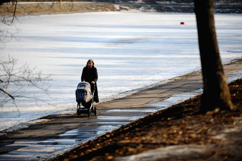 A woman takes a walk with her baby in Moscow, Russia, on March 11, 2015. Moscow embraced warm spring with its temperature hitting almost 10 degrees Celsius in the ...