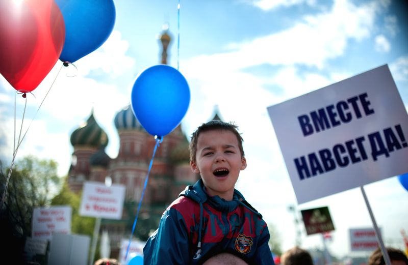 A boy attends a parade marking the International Labor Day on the Red Square in Moscow, on May 1, 2014. It was the first grand rally of the Labor Day on the Red Square