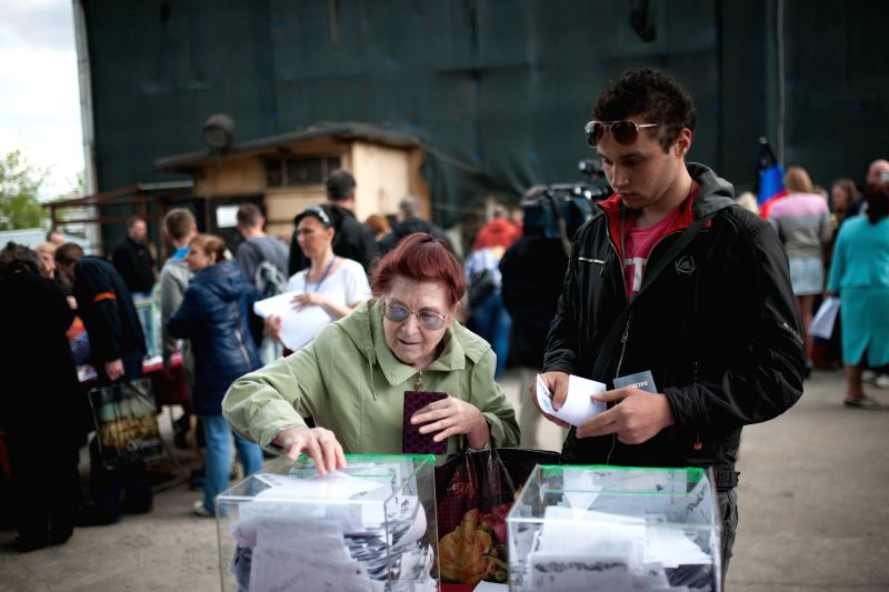 A voter casts her ballot at a polling station in Moscow, Russia, on May 11, 2014. A polling station was set up in Moscow for voters from Donetsk and Luhansk of ...