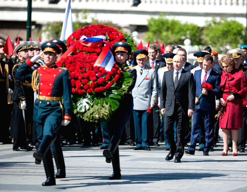 Photo: Russian President Vladimir Putin lays a wreath before the Eternal Fire at the Tomb of the Unknown Soldier during a wreath laying ceremony in the Alexandrovsky ..