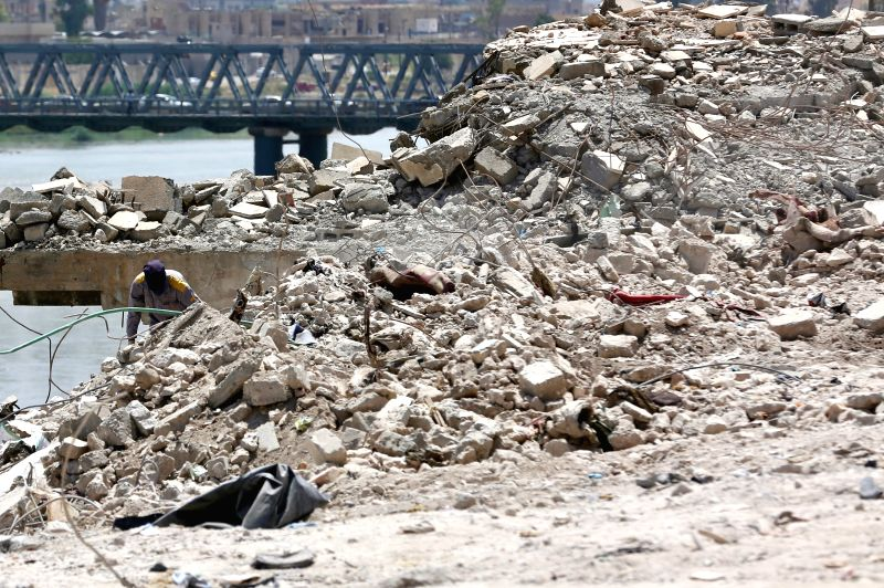 MOSUL, July 6, 2018 - A worker searches for bodies buried under debris at a spot in the old city of Mosul, northern Iraq, on July 5, 2018. More than 5,200 bodies have been retrieved during the past ...