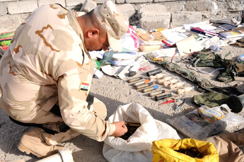 MOSUL, May 10, 2017 - An Iraqi soldier checks the seized arms and ammunition in the northwestern suburb of Mosul, Iraq, May 9, 2017.