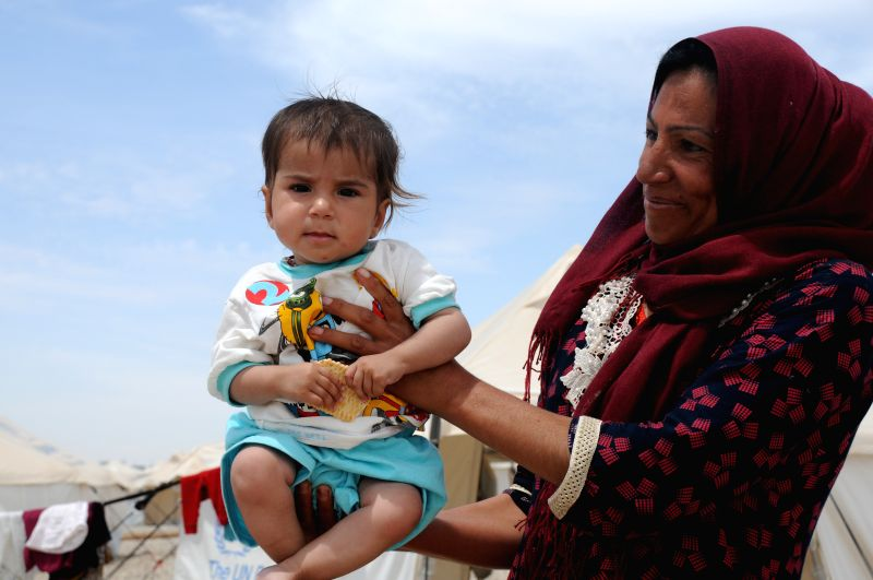 MOSUL, May 13, 2017 - A woman holds her child in Hassansham U2 Camp, about 30 km east to Mosul, Iraq, on May 13, 2017. The camp has a capacity to accommodate more than 9,000 people when fully ...