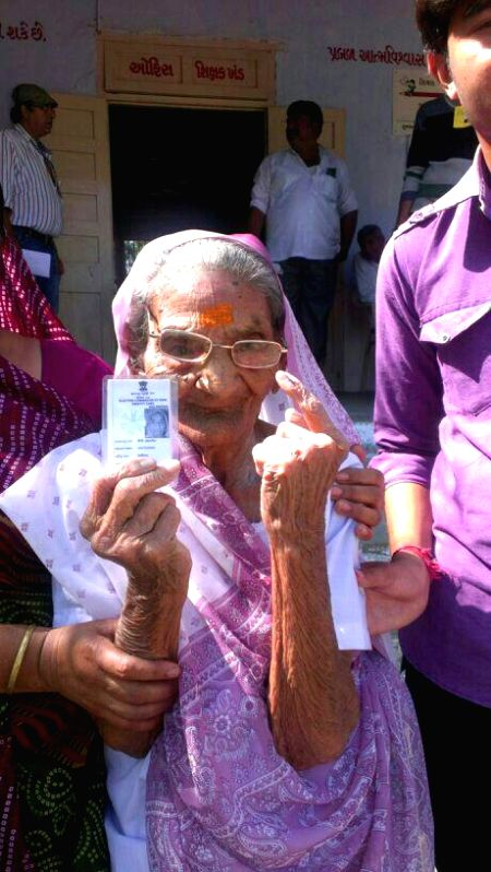 Mother of BJP Prime Ministerial candidate and Gujarat Chief Minister Narendra Modi, Heeraben shows her fore finger marked with phosphorous ink after casting her vote at a polling booth during the ...