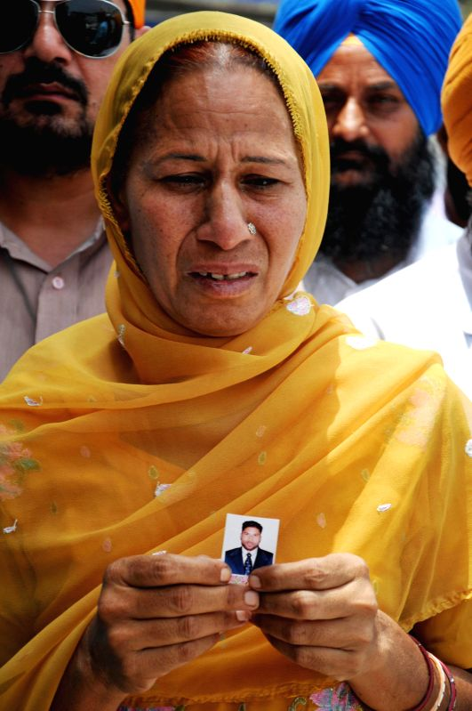 Mother of Dharminder Kumar who is believed to be trapped in violence-hit Iraq prays for his well being at the Golden Temple in Amritsar on June 19, 2014. - Dharminder Kumar