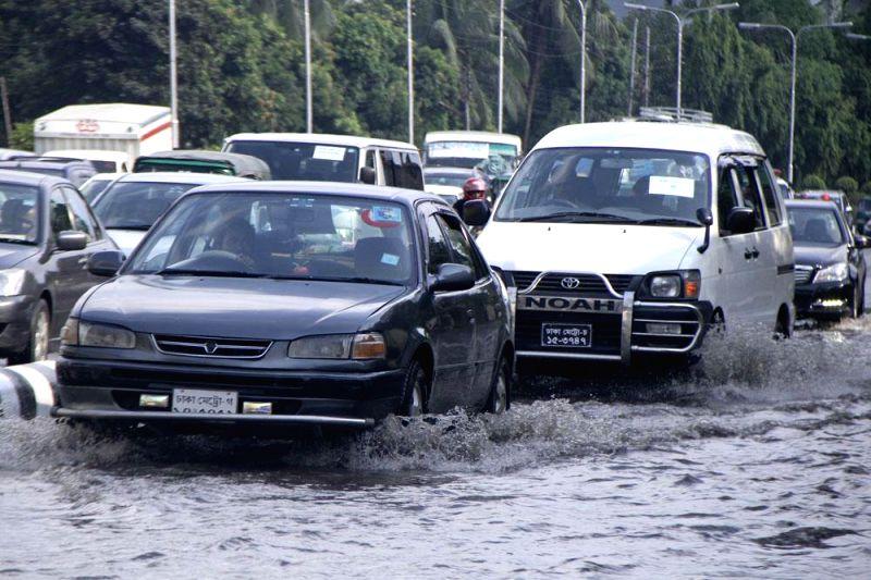 Motorists drive on a water logged street of Dhaka, Bangladesh on May 7, 2014.