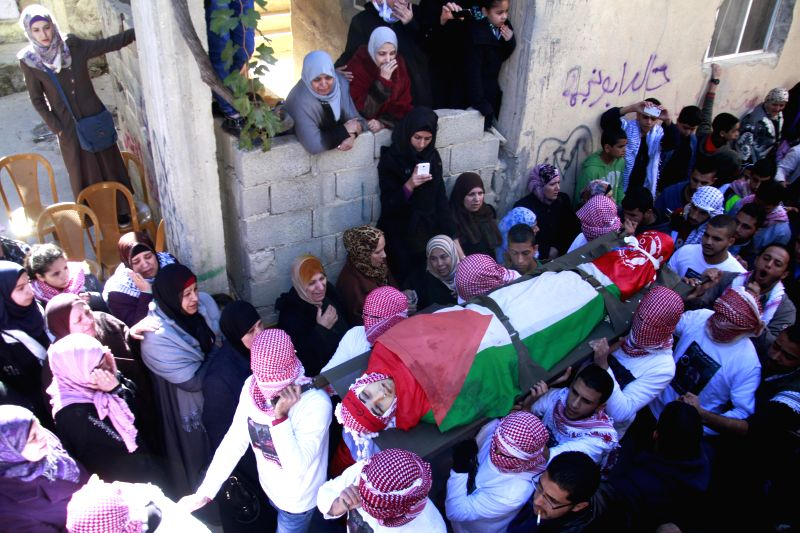 Mourners carry the body of Palestinian Malek Shahin, 21, who medics said was shot dead by Israeli troops while they were carrying out an arrest raid on Tuesday, ...
