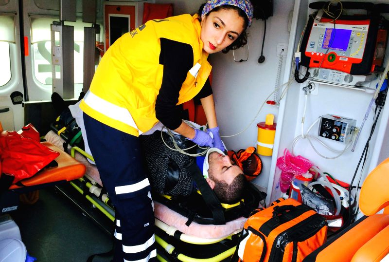 MUGLA (TURKEY), Feb. 7, 2015 A rescuer takes care of an injured migrant on an ambulance in western Turkey's Mugla province, on Feb. 7, 2015. At least seven people were killed, six injured