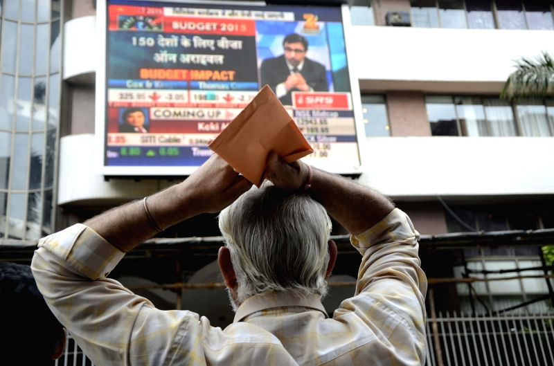 A man watches Union Finance Minister Arun Jaitley present the national budget for 2015-16 on a big screen outside Bombay Stock Exchange in Mumbai on Feb 28, 2015. - Arun Jaitley