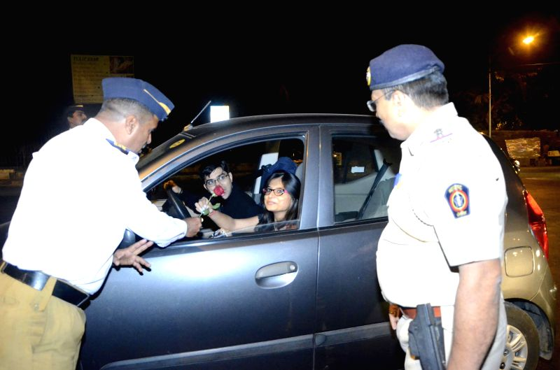 A policeman greets a lady with a rose on the new year's eve in Mumbai, on Dec 31, 2014.