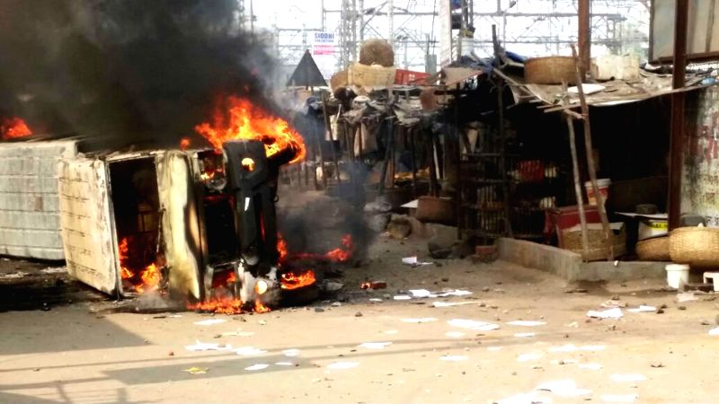 A vehicle burns as suburban train commuters stage impromptu agitation after train services were disrupted  during the the morning peak hour in Mumbai, on Jan 2, 2015. The technical hitch and .