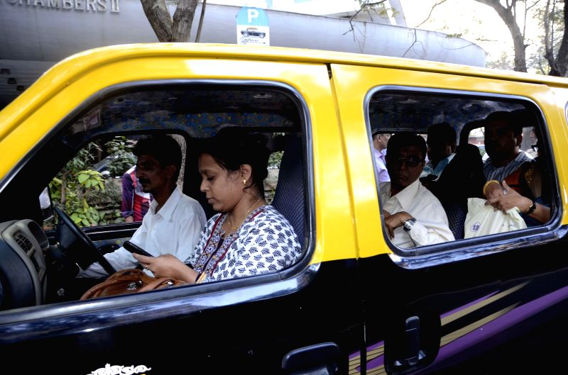 A woman sits on the front passenger seat of a taxi as Maharashtra Transport Minister Diwakar Raote launched `Bhagini Sanman` a new campaign in Mumbai under which the front passenger seats of . - Diwakar Raote