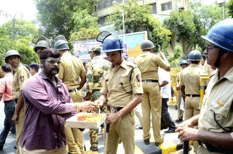 A worker of Republican Party of India distributes sweets to policemen on duty on Ambedkar Jayanti in Mumbai, on April 14, 2015.