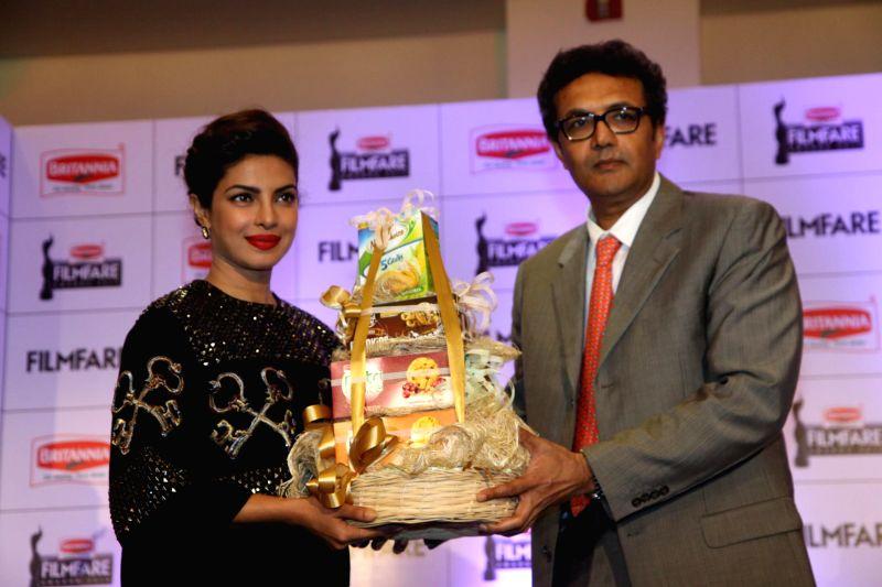 Actor Priyanka Chopra and Varun Berry, MD, Britannia Industries Ltd during the announcement of the 60th Britannia Filmfare awards in Mumbai on Sunday, Dec. 7, 2014. - Priyanka Chopra