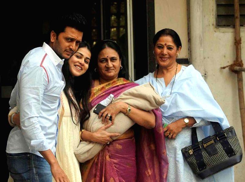 Actors Riteish Deshmukh and Genelia D'Souza with their son in Mumbai, on Nov 30, 2014. - Riteish Deshmukh and Genelia D'Souza