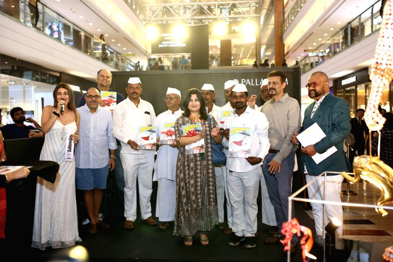"""Mumbai: Chef Anaida Parvaneh, Ullas Shantaram Muke and and Valay Shende with artist Abhijeet Kini during the launch of his comic book """"Dabbawala"""" at a mega-function held at restaurant chain SodaBottleOpenerWalaa's outlet in Palladium, Lower Parel in"""