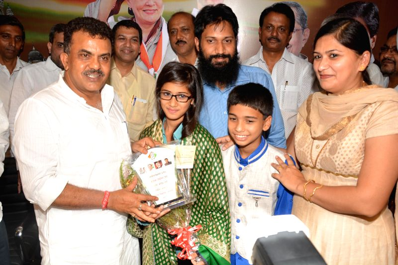 Congress leader Sanjay Nirupam felicitates Mariyam Asif Siddiqui who who won first prize in the Gita Champions League competition conducted by ISKCON in Mumbai on April 8, 2015.