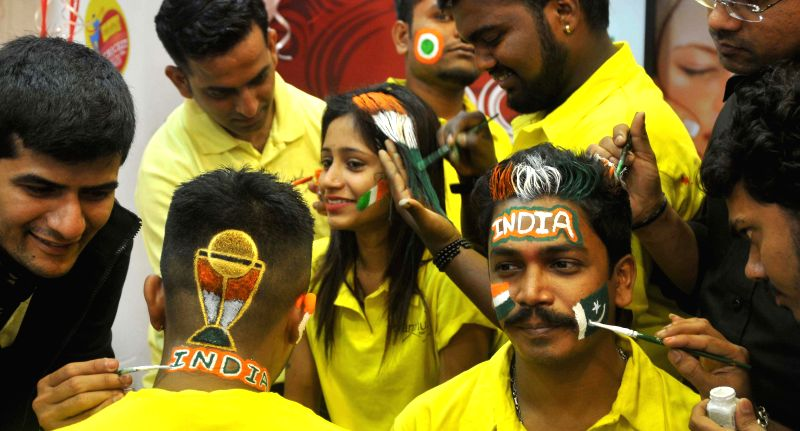 Cricket enthusiasts get their faces painted ahead of ICC World Cup 2015 in Mumbai, on Feb 12, 2015.