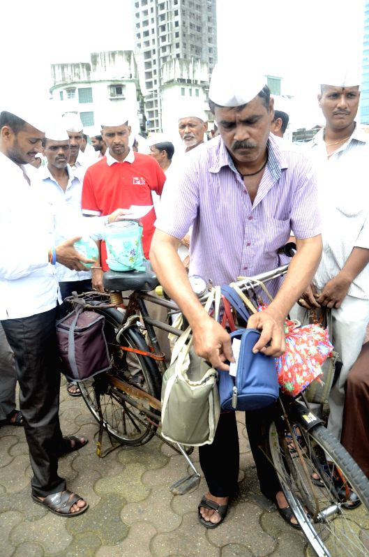 Mumbai Dabbawalas puting campaign materials in tiffin boxes for donation in Chief Minister`s Relief Fund for Malin landslide victims in Mumbai on August 02, 2014.