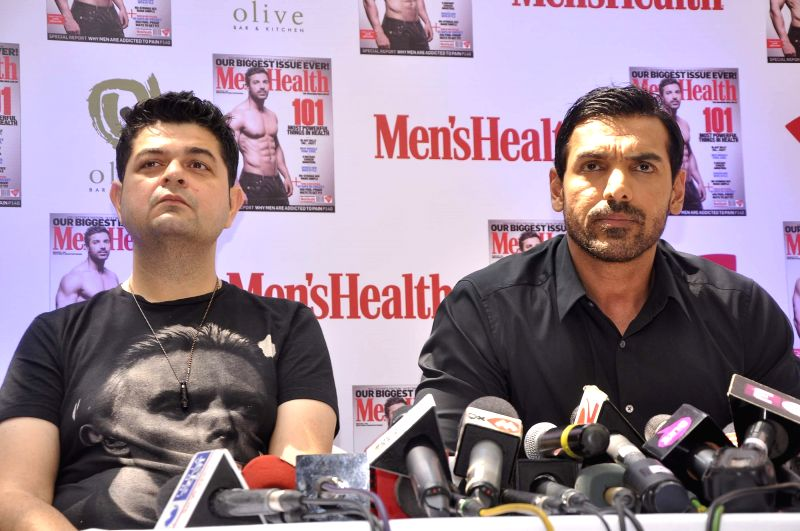 Fashion photographer Daboo Ratnani and actor John Abraham during the unveiling of Men`s Health magazine`s latest cover in Mumbai on March 11, 2015.