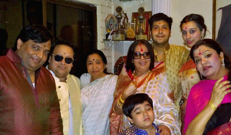 Govind Bansal, Bappi Lahiri, Asha Bhosle, Bappa Lahiri, Chitrani Lahiri, Tanisha Lahiri, Rema Bansal and kid Swastik Lahiri at Bappi Lahiri`s Saraswati Puja at his residence in Mumbai on Jan . - Asha Bhosle